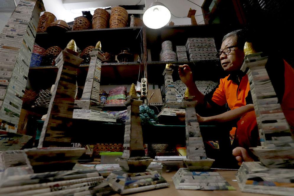 Sugito (68) menyelesaikan pembuatan miniatur Monas dari kertas koran bekas di Bank Sampah Tri Alam Lestari, Pesanggrahan, Jakarta Selatan,Kamis, 10 Juni 2021. Foto: Ismail Pohan/TrenAsia\n
