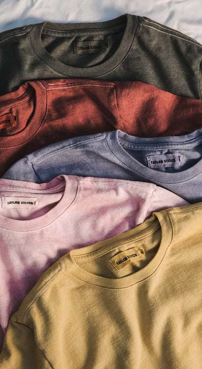 A close up shot of a handful of colorful naturally-dyed tees.