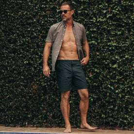 fit model wearing The Adventure Short in Navy from Taylor Stitch, standing by pool, shirt unbuttoned