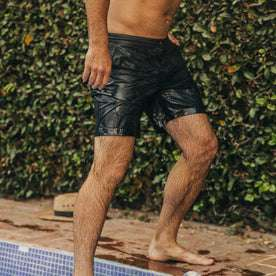 fit model wearing The Adventure Short in Navy from Taylor Stitch, walking out of pool