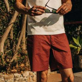 fit model wearing The Adventure Short in Rust, holding sunglasses