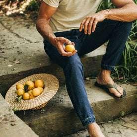 fit model wearing The Apres Pant in Indigo, sitting on steps holding lemon