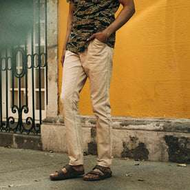fit model wearing The Camp Pant in Khaki Herringbone, against yellow wall