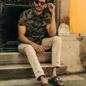 fit model wearing The Camp Pant in Khaki Herringbone, sitting on steps