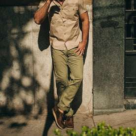 fit model wearing The Camp Pant in Olive Herringbone, against wall
