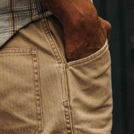 fit model wearing The Camp Short in Khaki Herringbone, hand in pocket, close up shot