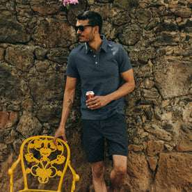 fit model wearing The Camp Short in Navy Herringbone, holding beer, next to yellow chair