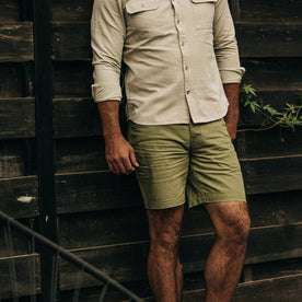 fit model wearing The Camp Short in Olive Herringbone, against wall