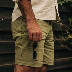 fit model wearing The Camp Short in Olive Herringbone, holding sunglasses