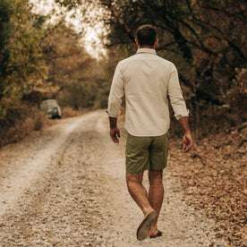 fit model wearing The Camp Short in Olive Herringbone, walking away from camera