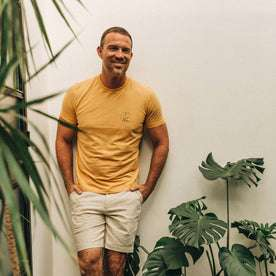 fit model wearing The Cotton Hemp Tee in Canary Eagle, looking right