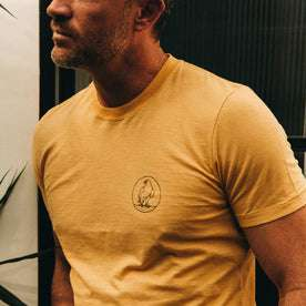 fit model wearing The Cotton Hemp Tee in Canary Eagle, cropped shot of chest