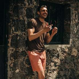 fit model wearing The Cotton Hemp Tee in Espresso Todo Chido, smiling, holding sunglasses