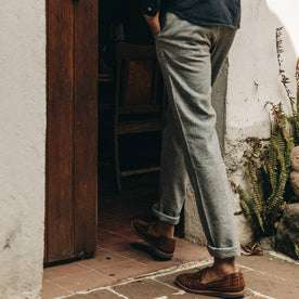 fit model wearing The Easy Pant in Navy Herringbone, cuffed with shoes, walking indoors