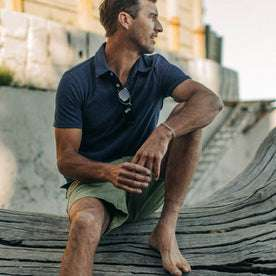 fit model wearing The Heavy Bag Polo in Navy Stripe, sitting on wood