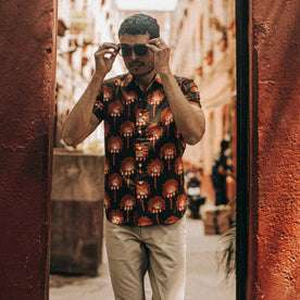 fit model wearing The Short Sleeve Hawthorne in Mirage Palm, touching sunglasses
