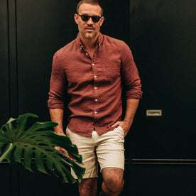 fit model wearing The Jack in Rust Linen, looking at camera, next to plant