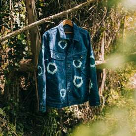 outdoor material shot of The Long Haul Jacket in Hand-Dyed Indigo, hanging on branch