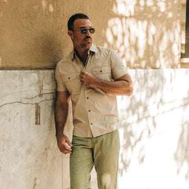 fit model wearing The Short Sleeve Officer Shirt in Khaki, leaning against wall