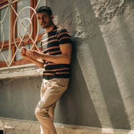 fit model wearing The Organic Cotton Tee in Coal and Rust Stripe, against wall