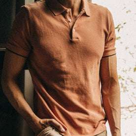 fit model wearing The Pique Polo in Coral, chest detail