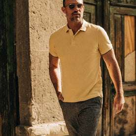 fit model wearing The Pique Polo in Straw, hand in pocket, walking