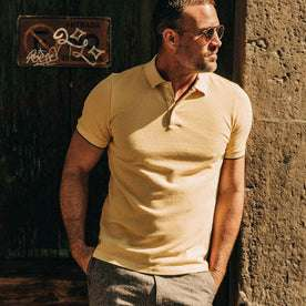 fit model wearing The Pique Polo in Straw, looking right