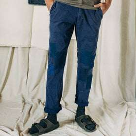 material shot of The Atelier and Repairs Chino in Navy, cuffed on model, in a studio