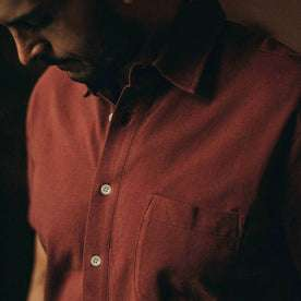 fit model wearing The Short Sleeve California in Rust Pique, up close shot of chest, looking down