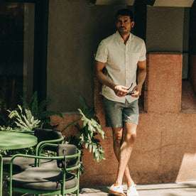 fit model wearing flatlay of The Short Sleeve Jack in Natural Ramie Grid, looking at camera, holding sunglasses