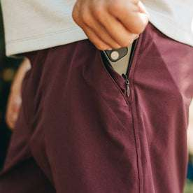 fit model wearing The Traverse Short in Wine, putting phone in pocket