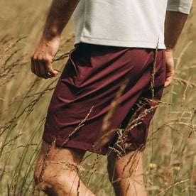 fit model wearing The Traverse Short in Wine, side profile in field