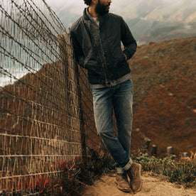fit model wearing The Democratic Jean in in 18 Month Wash Organic Selvage, leaning against fence