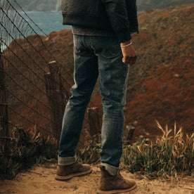 fit model wearing The Democratic Jean in in 18 Month Wash Organic Selvage, standing in dirt
