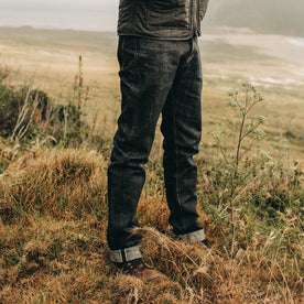 fit model wearing The Democratic Jean in Nihon Menpu Selvage, standing on grass