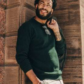 fit model wearing The Double Knit Sweater in Forest, leaning agains wall