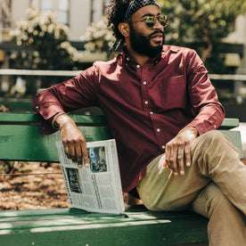 fit model wearing The Jack in Burgundy Oxford, holding newspaper