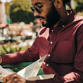 fit model wearing The Jack in Burgundy Oxford, reading paper