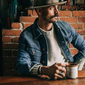 fit model wearing The Long Haul Jacket in 18-Month Wash Organic Selvage, drinking coffee