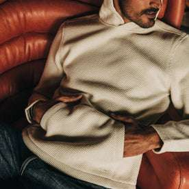fit model wearing The Nomad Hoodie in Natural Twill hands in pocket, reclining