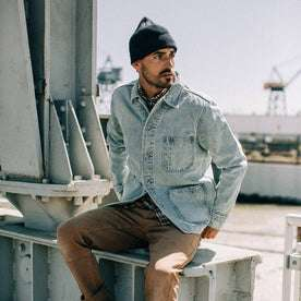 fit model wearing The Ojai Jacket in Washed Denim, sitting, looking right