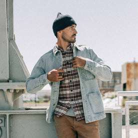 fit model wearing The Ojai Jacket in Washed Denim, layered over flannel, looking right