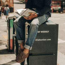 fit model wearing The Slim Jean in 18 Month Wash Organic Selvage, sitting on newspaper box