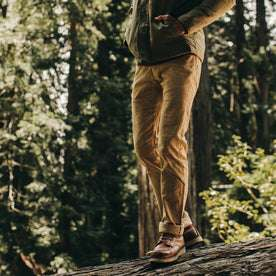 fit model wearing the all day pant, walking on log