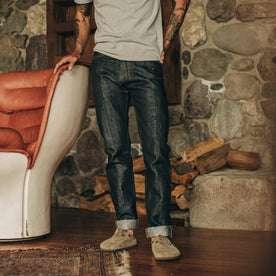 fit model wearing The Slim Jean in Nihon Menpu Selvage, standing next to chair