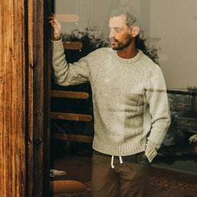 fit model wearing The Topside Sweater in Natural Cable Knit, looking through window