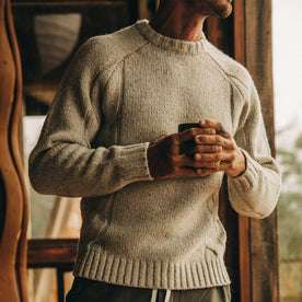 fit model wearing The Topside Sweater in Natural Cable Knit, holding coffee
