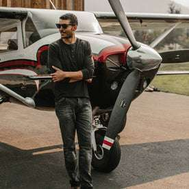 fit model wearing The Merino Henley, leaning against plane