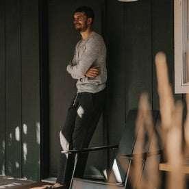 fit model wearing The Merino Henley, leaning against doorframe