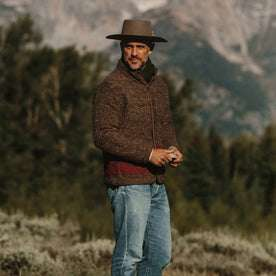 fit model wearing The Port Jacket in Espresso Marl, holding rock